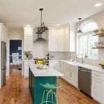 green kitchen island surrounded by white kitchen cabinets
