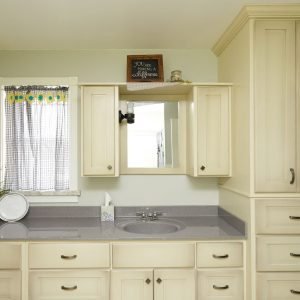 off-white bathroom cabinets with a bathroom sink and window